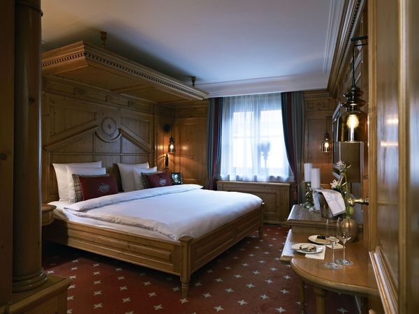 "A large, traditionally furnished ""Bavarian Suite"" in the Platzl Hotel Munich with a four-poster bed and wood panelled walls"