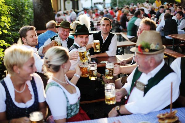 Several people in traditional Bavarian costume sit on beer benches in a beer garden and toast together