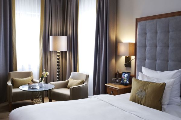 "In a ""Deluxe Double Room"" in the Platzl Hotel Munich there is a double bed with a large leather headboard and three different pillows"