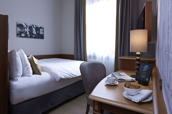"A bright ""Queen bed single room"" in the Platzl Hotel Munich with a large window"