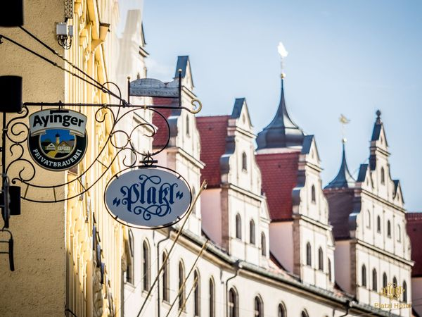 A view along the facades of houses in Munich, on which the logo of the Ayinger brewery and a logo of the Platzl Hotel Munich hang