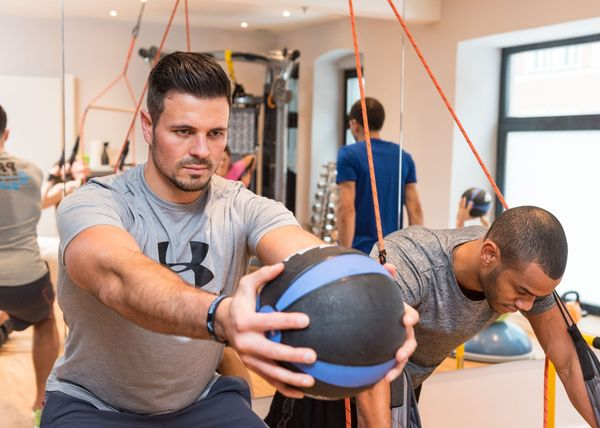 Two young men do different sports exercises in the BiPhit-Studio, which is located in the Platzl Hotel Munich