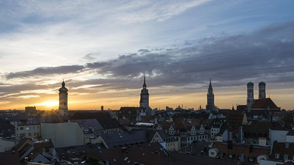 The skyline of Munich at sunrise with the tower of the old and new town hall, the old Peter, the Frauenkirche and the Heilig-Geiste Kirche