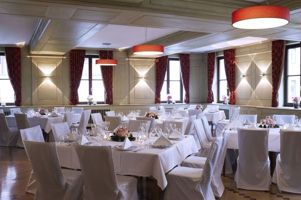 "In the large ""Marktplatzl"" in the Platzl Hotel Munich, there are several festively set tables, each with room for 8 people"