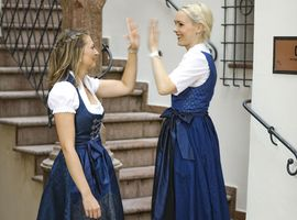 Two ladys wearing the Bavarian typical costume and doing an hi5